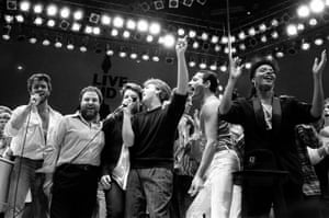 George Michael, concert promoter Harvey Goldsmith, Bono, Paul McCartney, Bob Geldof and Freddie Mercury join in the finale of the Live Aid famine relief concert at Wembley Stadium in London on 13 July 1985.