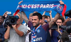 Dani Alves poses with a scarf after a press conference in Paris.
