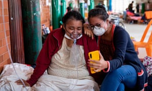 A COVID-19 patient breathing with the assistance of oxygen and her daughter talk to relatives through a mobile phone at the regional hospital in Iquitos, the largest city in the Peruvian Amazon, on 9 May 2020 during the novel coronavirus pandemic.