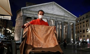A waiter removes a table as he prepares to close a bar in front of the Pantheon in Rome.
