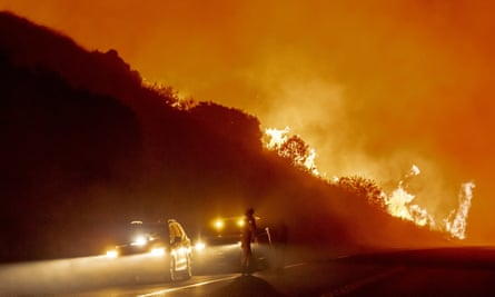 Vehicles are pulled off to the side of the road as the Bond Fire, driven by high winds, approaches Santiago Canyon Road in California on Thursday.
