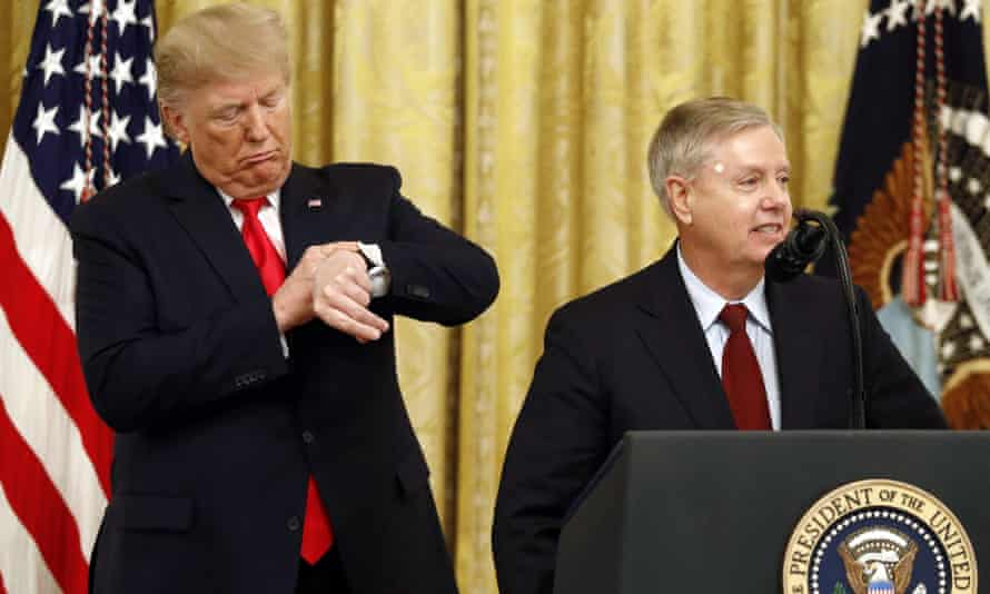 Donald Trump pretends to check his watch as Senator Lindsey Graham speaks at the White House in November.