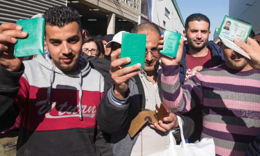 Laid-off workers show their Palestinian identity cards as they leave the SodaStream plant in Israel for the last time.