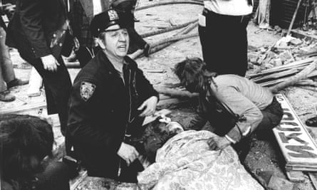 A New York City police officer calls for help as he kneels near a victim of the Fraunces Tavern bombing.