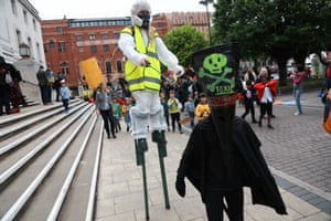 Two young activists, one dressed as a council worker with a weedkiller spray and one dressed as the poisonous glyphosate.