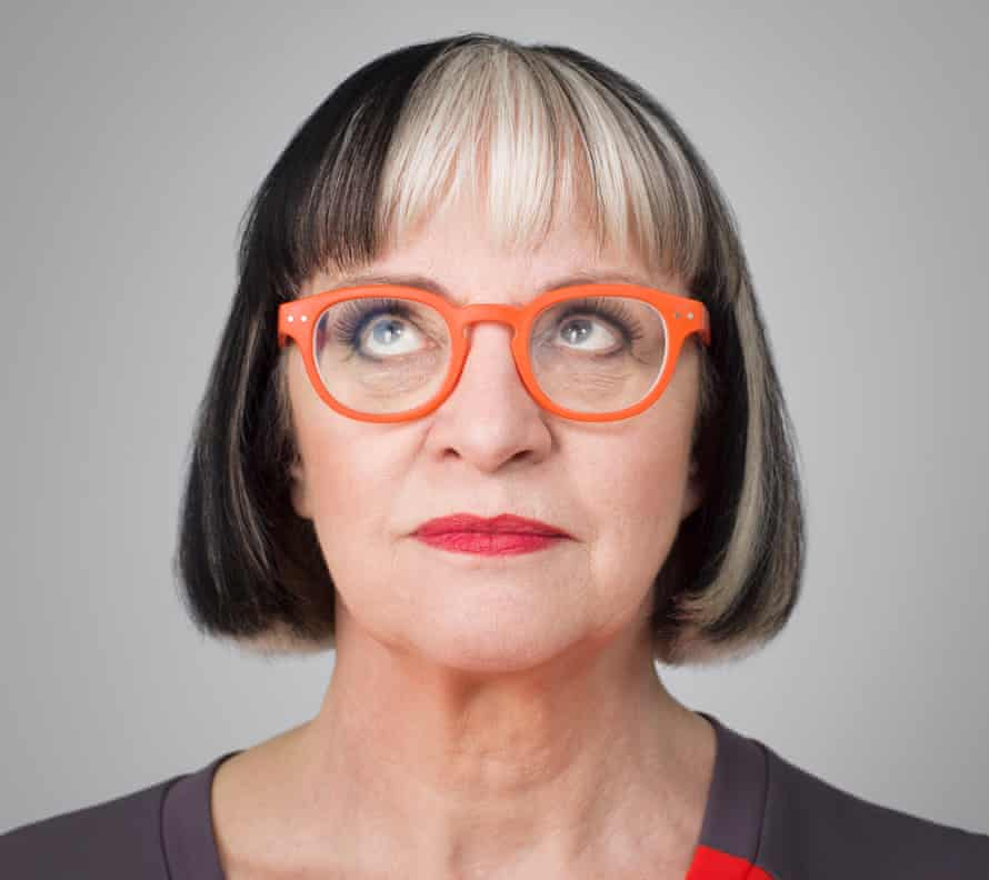 Close up of Philippa Perry in plastic orange-rimmed glasses and red lipstick, looking up