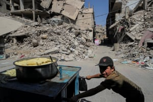 A child pushes a cart selling cooked sweetcorn in Douma amid the rubble of the former rebel-held town