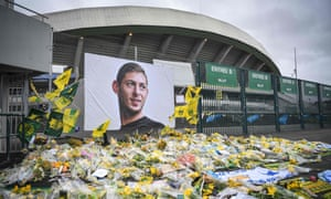 Yellow flowers are displayed in front of a portrait of Emiliano Sala at the Beaujoire stadium in Nantes, France.