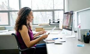 Side view of businesswoman video conferencing with female colleague over desktop computer