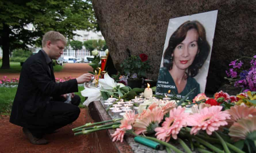 A man lights a candle in front of a portrait of the journalist Natalia Estemirova in St. Petersburg in 2009.