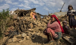A family in front of their destroyed home in Kathmandu