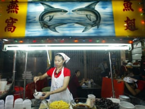 A vendor prepares a bowl of soup at a stall serving shark's fin soup and other Chinese delicacies, late 09 February 2005 in Bangkok's Chinatown
