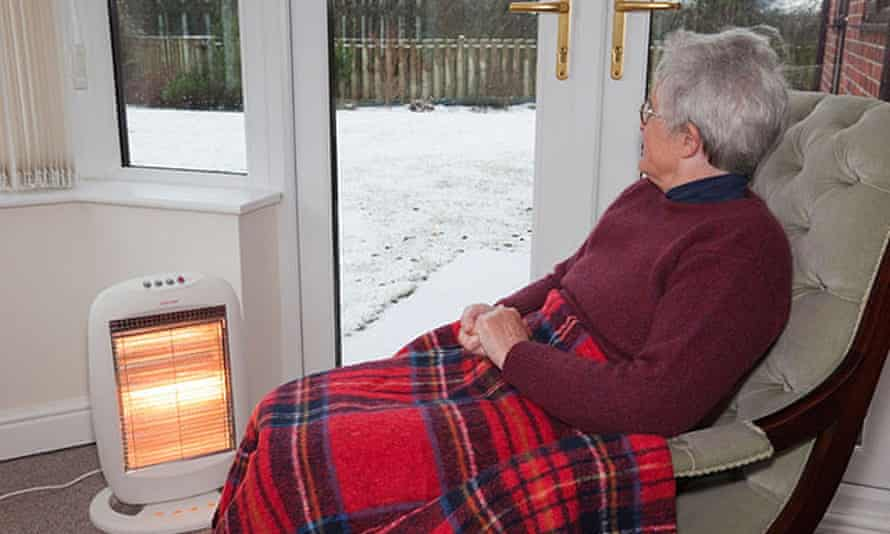 Elderly old woman at home with a rug on knees keeping warm indoors