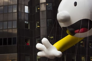 People watch as the Diary of a Wimpy Kid balloon makes its way across Sixth Avenue