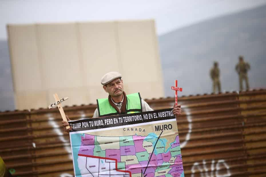 A man in Tijuana holds a sign during a protest near the prototypes of the US-Mexico border wall.