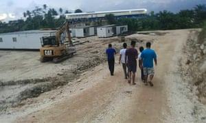 A group of refugees and asylum seekers walk by a construction site at the East Lorengau centre on Manus Island.