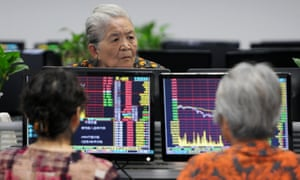 Investors monitor stock prices at a securities company in China's central Jiangxi province today