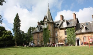 Widescreen shot of Chateau de la Baudonniere in Normandy, near Les Chambres, France. The image shows families eating outside the chateau, communally.