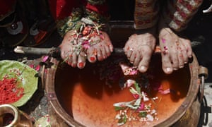 A Nepalese bride and groom place their feet above a vat during a wedding ceremony at a Hindu temple