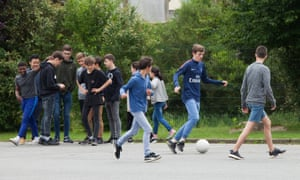Children play football and chat in the playground.