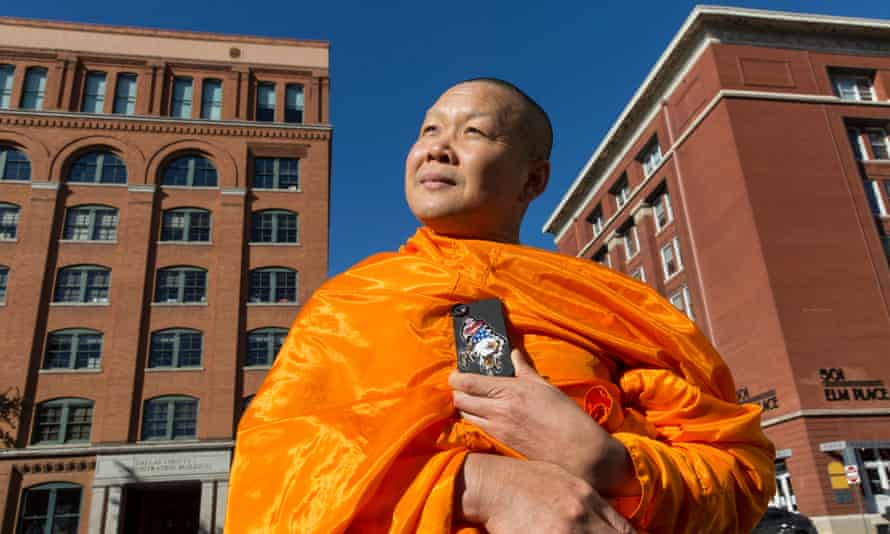 Somboon Rattanawerapong, 47, a buddhist monk from Thailand who lives in Arlington, Texas, visits the Texas School Book Depository and surrounding streets that mark the events where JFK was assassinated by Lee Harvey Oswald. Somboon proudly displays his mobile phone case which has a Texan eagle design on it. He says it is because he is known as the King Eagle of Texas!