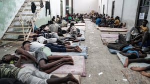 People lie on mats at a detention centre in Zawiyah, near  Tripoli, in June 2017