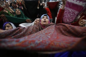 A Kashmiri Muslim woman raises her veil in air to pray as thousands of Kashmiri Muslims the Hazratbal shrine, which houses a relic believed to be a hair from the beard of Prophet Muhammad