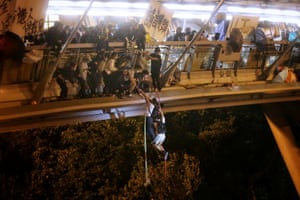 Anti-goverment protesters abseil onto a highway to escape