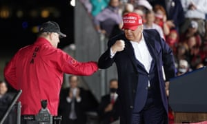 Donald TrumpPresident Donald Trump bumps elbows with Dan Gable during a campaign rally at Des Moines International Airport in Iowa.