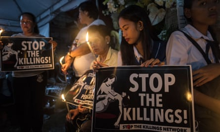 Classmates of 17-year-old student Kian Delos Santos, who was killed allegedly by police officers during an anti-drug raid, light candles at Kian's wake in Manila on August 25, 2017