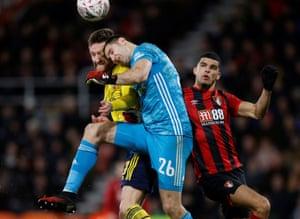 Arsenal's Emiliano Martinez and Shkodran Mustafi collide.
