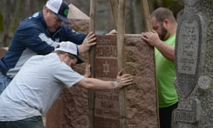 Volunteers from a local monument company help to reset vandalized headstones at Chesed Shel Emeth Cemetery.