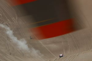 A helicopter propeller is seen in the top of the image as participants race below