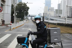 Delivery worker for Alibaba's Hema Fresh chain rides his electric bicycle on a road following an outbreak of the novel coronavirus in Wuhan.