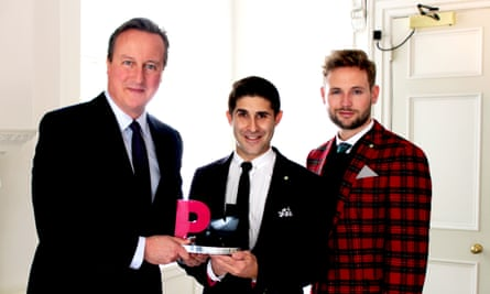 David Cameron receives his award from PinkNews chief executive Benjamin Cohen and fiance Dr Anthony James.