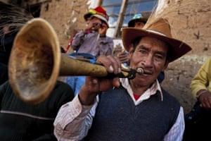 A Peruvian plays a trumpet during the Yawar Fiesta.