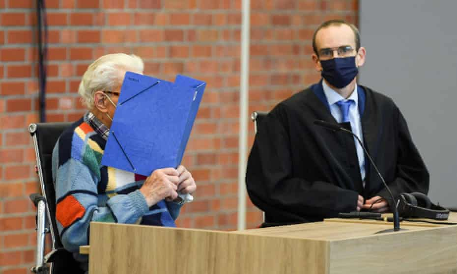 The accused, Josef S (left), covers his face in the court room in Brandenburg.