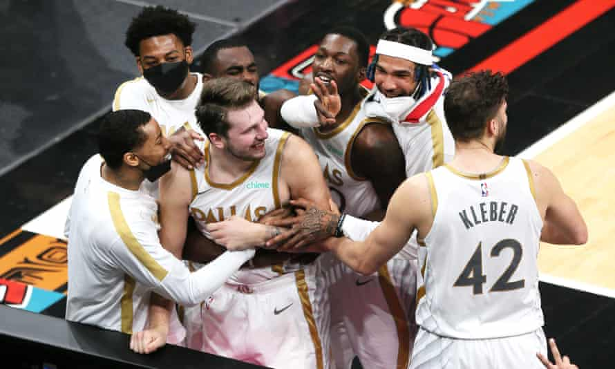 Luka Doncic celebrates with his Mavericks teammates after making the clinching shot against the Grizzlies