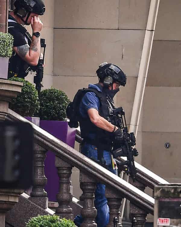 Armed officers leave the Park Inn on 26 June in Glasgow.