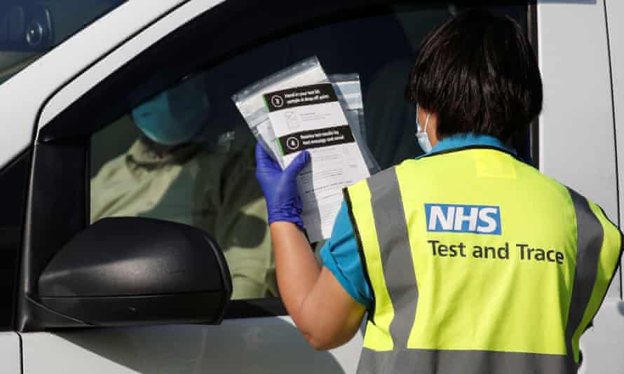 an NHS test and trace worker chats with a driver at a testing centre