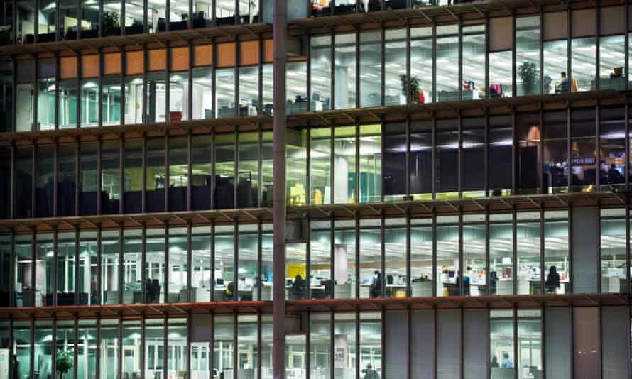 View into office building<br>Workers at their cubicles in an office building working late at night.