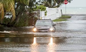 A car drives through a flooded street in Nassau.