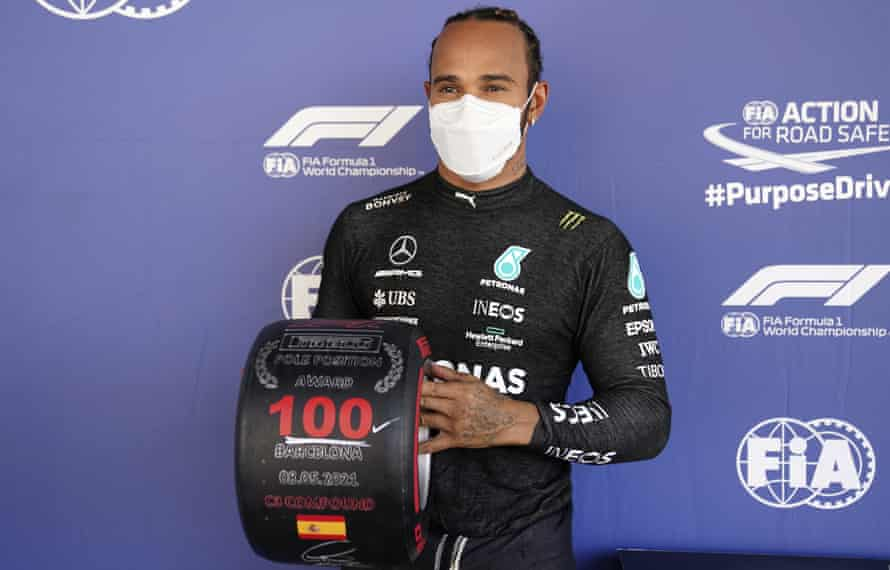 Lewis Hamilton poses with a trophy marking his 100th career pole position in Formula One.