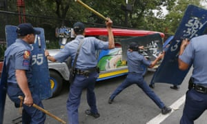 Police officers hit fleeing protesters outside the US embassy in Manila