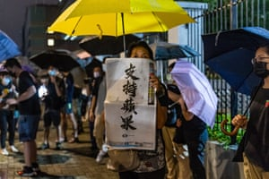 A supporter holds up a copy of the Apple Daily newspaper outside its offices in Hong Kong