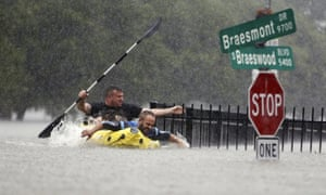 Two kayakers try to beat the current pushing them down an overflowing Brays Bayou.