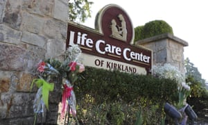 Flowers left next to the sign that marks the entrance to the parking lot of the Life Care Center in Kirkland.