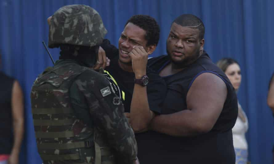 The son of 46-year-old Evaldo dos Santos Rosa grieves at the scene in the Guadalupe neighborhood, in Rio de Janeiro, Brazil, on 7 April.