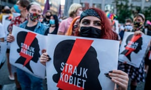 Protesters hold banners reading 'women's strike' as they march in Warsaw