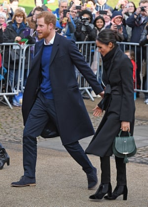 Meghan Markle with Prince Harry, wearing a Stella McCartney coat, Hiut jeans and a DeMellier London handbag